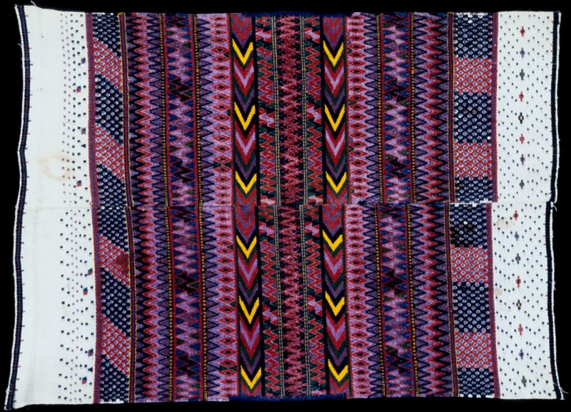 fabric piece; 2 pieces with 4 selvages each seamed at center; bands of multicolored zig-zag design created by supplementary weft