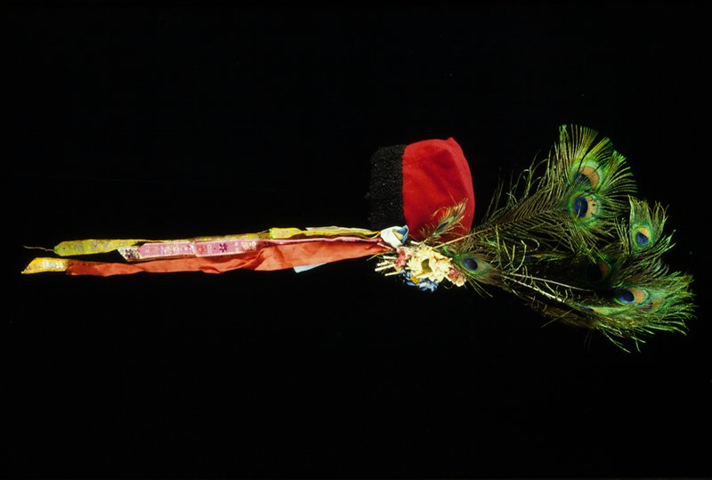four-cornered man's hat; red with black wool trim; peacock feathers with fabric flowers, embroidered ribbon streamers