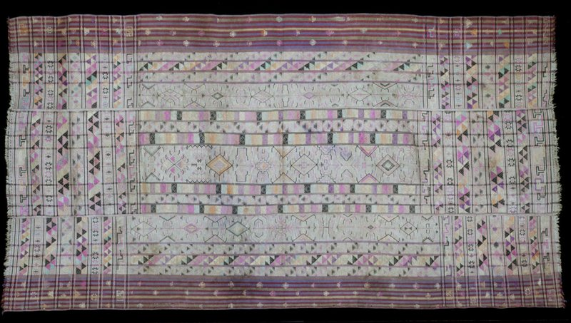 Kira, Kushotara; silk/cotton brocade on white cotrton background, L.92 in., W.50 in. 3 panels; discontinuous supplemmental weft design in pink, purple, black, salmon on neutral ground with stripes of red, blue, green, yellow at borders; fringe.