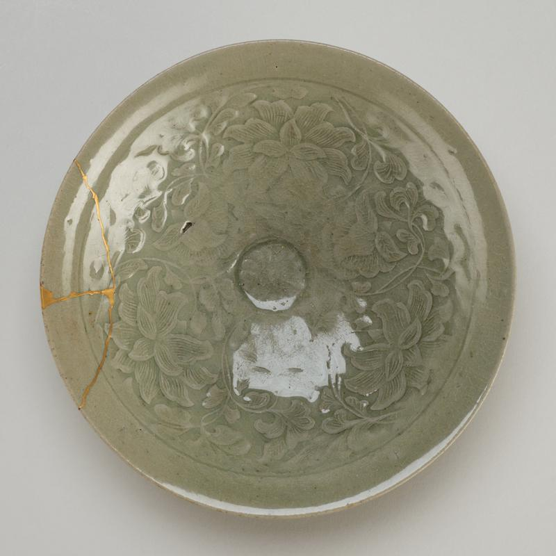 bowl coniform with shallow ring foot; interior decorated with molded floral medallion and peonies and vines; celadon, grey-green