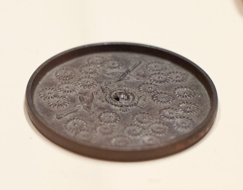 mirror round with pair of flying cranes embossed in relief and surrounded by chrysanthemums