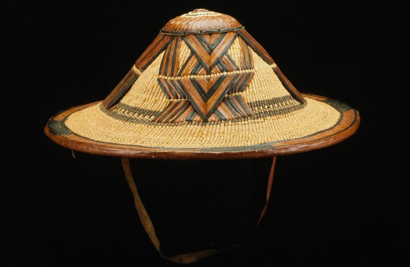large hat, basketry base, brown, black and cream leather woven in geometric patterns around crown, plain leather chinstraps