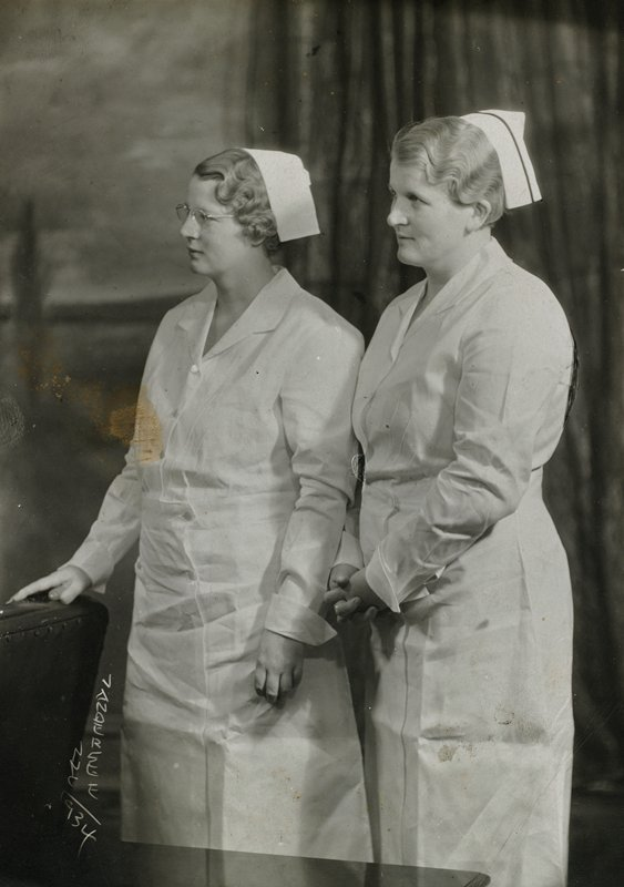 two nurses in profile, both standing, wearing white uniforms and white caps.
