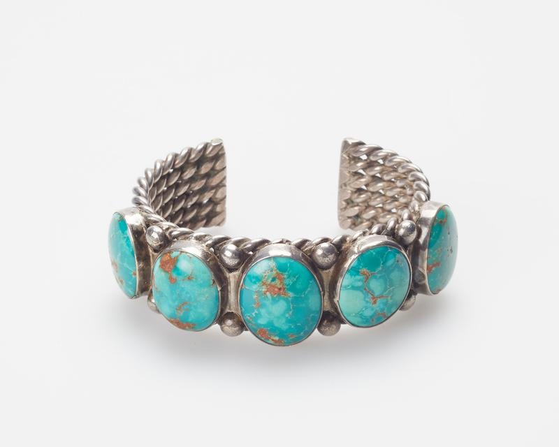 Navajo; 6 strands of double twisted wires;set with 5 elliptical Arizona turquoises; silver drops. J.#369, Cat.#197.