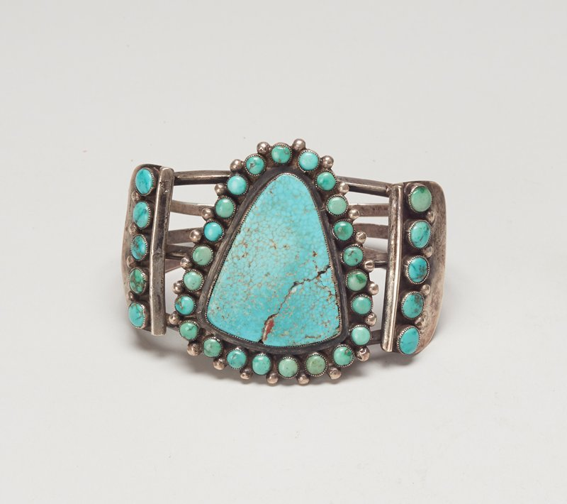 Three carinated wires; set with flat triangular turquoises surrounded by twenty-three round turquoises and flanked by vertical rows of five stones each; finely serrated bezels; teardrop decoration; 3 Bands; shield-shaped central turquoise shurrounded by small stones cat. 146, J#22