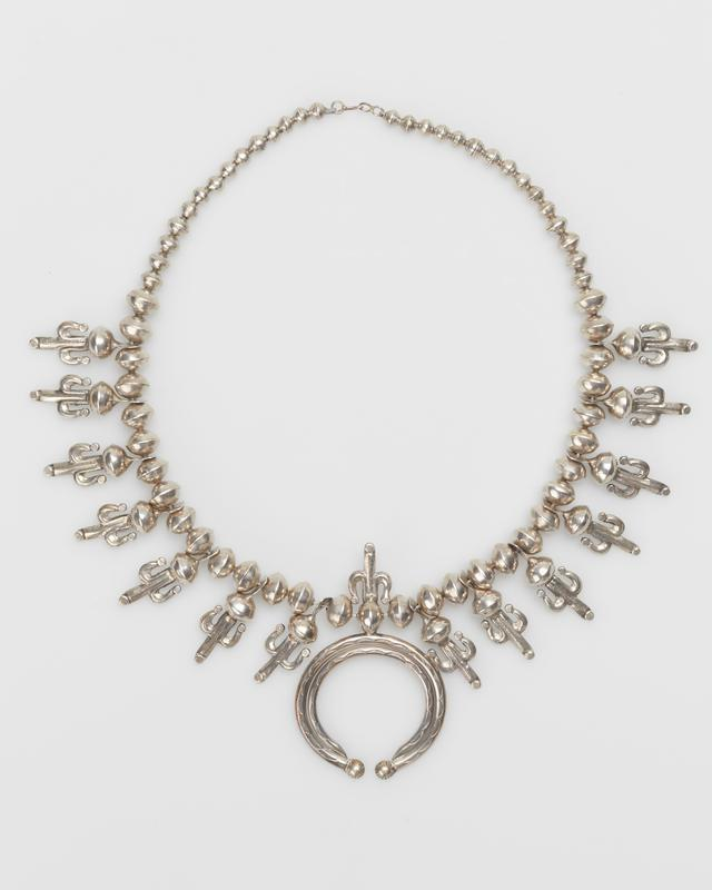 Single strand of graduated silver beads; 14 cast corn-tassles attached to beads with triangular, pierced extensions; stamped naja of half-round wire with corn tassle on top. J.#441, Cat.#478.