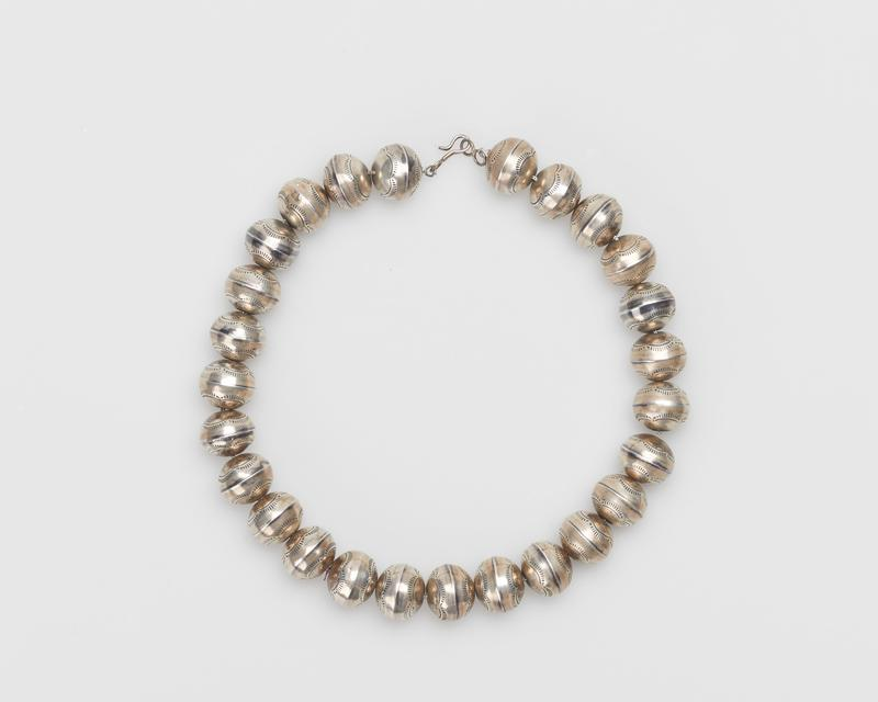 Single strand of slightly flattened silver beads; stamped design strung on silver chain, silver clasp. J.#418, Cat.#408.