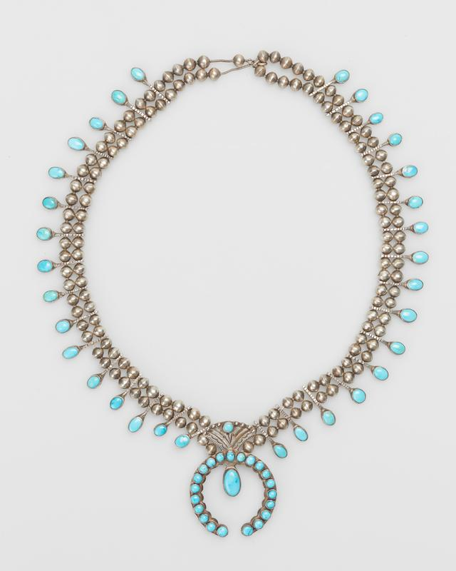Double strand of silver beads; 16 side turquoise on each side of naja in circular bezels; naja with 21 stones, large stone as pendant, fan shaped top with single stone and stamped design; silver chain and clasp; 55 stones. (Lone Mountain turquoises) J.#447, Cat.#432.