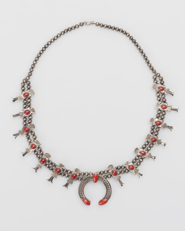 Single strand of silver beads changing to double; 14 butterfly squash blossoms with stamped designs and set with coral, 3 prongs on ea. side; 17 coral in all; 3 oval corals on two square wire enclosing double twisted wire naja. J.#499, Cat.#423.