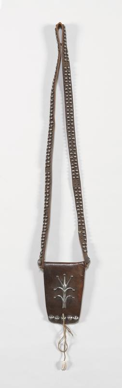 Cast silver ornament and repousse buttons on flap; Leather bag with leather strap, 2 rows plain and 2 larger silver fluted hogan buttons on strap; shell attached to thong hanging from purse. J.#520, Cat.#640.