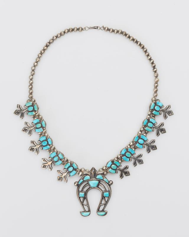 Ten flat cash squash blossoms of variant types set with Blue Gem turquoises of various shapes; double strand of spherical beads; cast triple naja set with Blue Gem turquoises; serrated bezels. J.#479, Cat.#440.