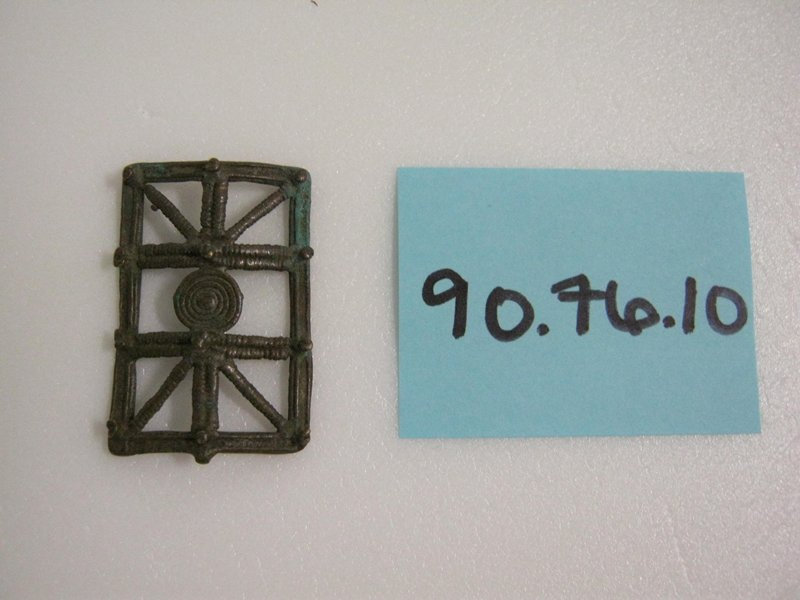 Open rectangular shaped sheild. Swirl in the center with round pegs around the outside.