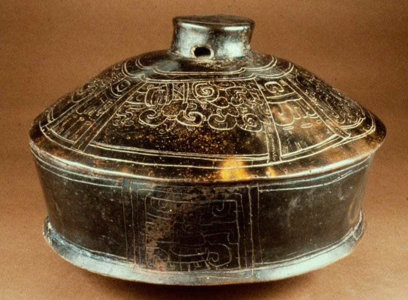 covered pot with incised design around dome-shaped lid, central knob with hole through center; body has straight sides rising from sharply slanting bottom; 4 decorative rectangles with incised design on sides; pottery-beige clay with burnished brown slip