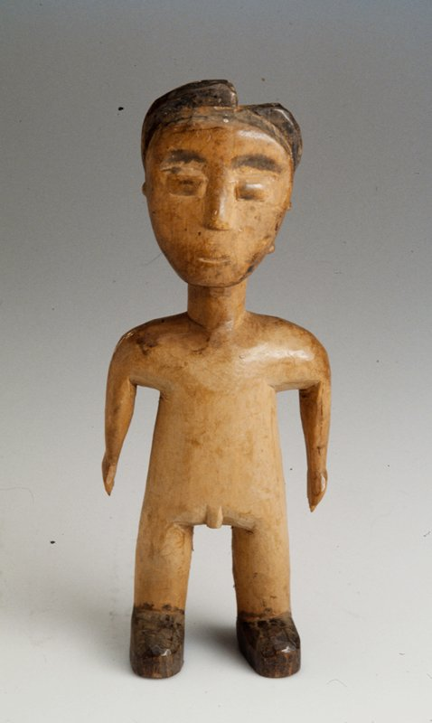 Wooden male figure; dark hair that has a part in it; black facial features and shoes;