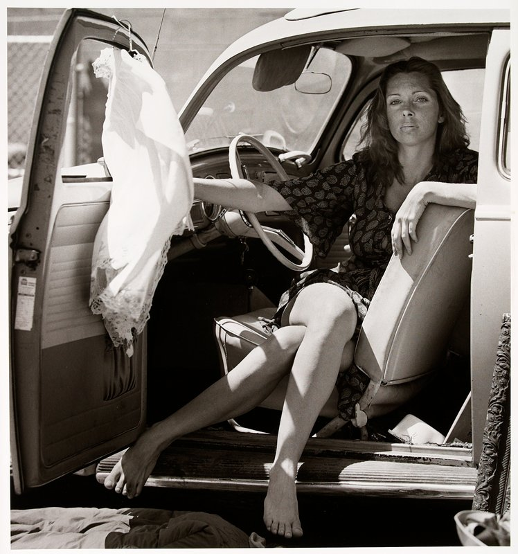 woman seated sideways on the driver's side of a car looking out the open door