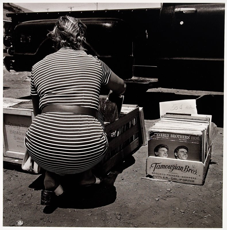 squating woman in horizontal striped dress looking through LPs in crates