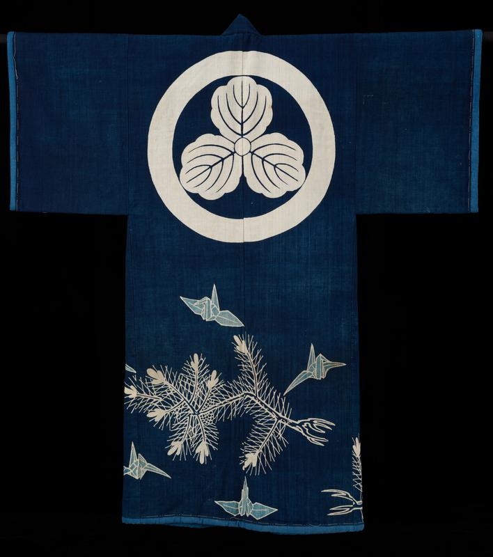 coverlet in the shape of a kimono; indigo field decorated with cranes and pines and a large crest or medallion on the top of the back