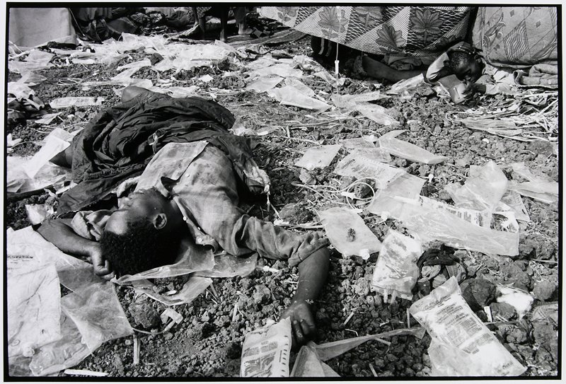 man laying on pebbled ground, surrounded by hospital I.V.s and I.V. bags