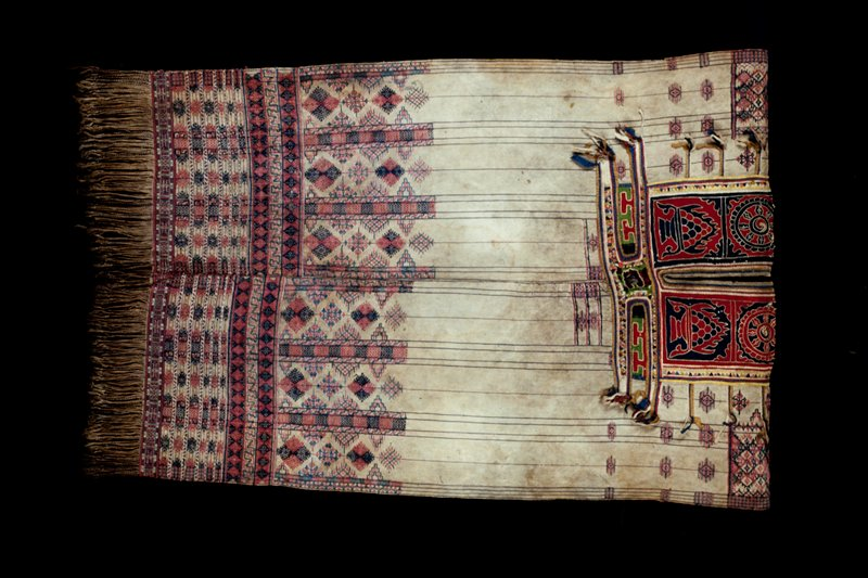 tunic with a tan field; body has vertical thin red and blue striping; shoulders and around waist supplementary weft patterning of bands decorated in blue and red geometric designs; cloth design in red and blue around neck with ribbons of fabric grouped along edges (extensions of the design)