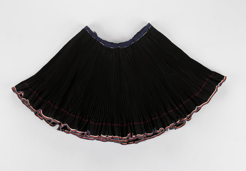 black wrap skirt with small pleating and red, white and blue trim; two long twine waist ties
