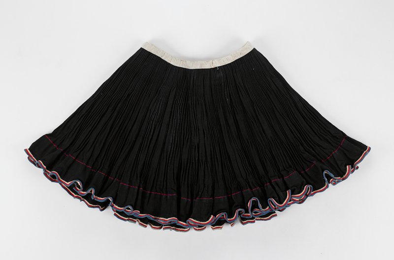 black wrap skirt with small pleating and red, white and blue trim; two long black tie strings