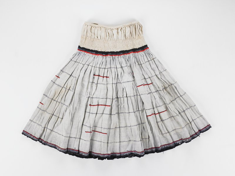 skirt with tan waistband, rest of skirt is tan, dark and light blue striped; red trim at bottom of waistband and near hem; red trim also in various other places
