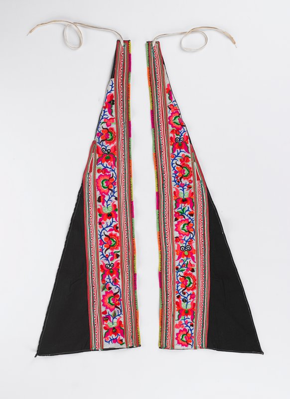 long triangle with ties on the furthest point; two thick bands of thin ribbon decoration between bands is an embroidered floral design band