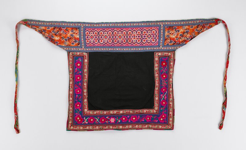 waistband decorated with large band of embroidery showing geometric patterns in fuchsia, green, orange and purple; main body of black fabric decorated with three embroidered bands and ribbons forming a squared 'U' shape; large central band shows fuchsia flowers on blue ground