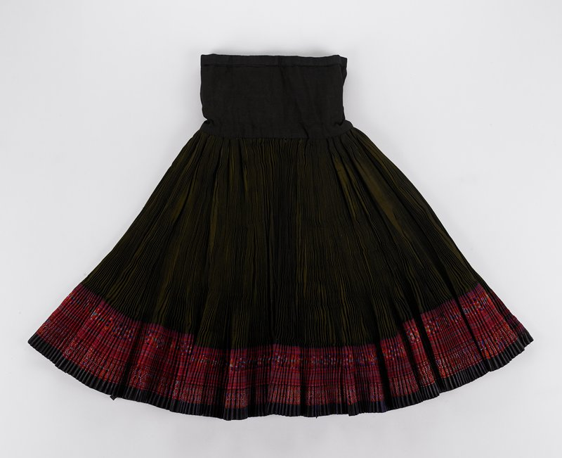 dark green pleated skirt with dark blue waistband and bands of embroidered ribbons near bottom hem