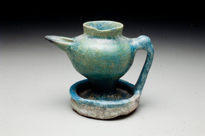 saucer base; strap handle; formed spout; blue glaze