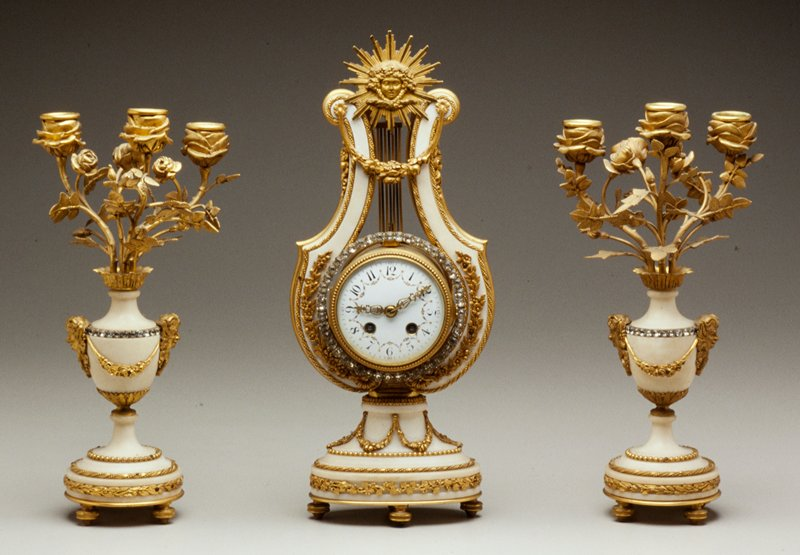 three piece clock garniture; white marble with ormolu mounts of sunburst and floral scrollwork, pendulum swing; circle of rhinestones around clock; two three-branch candlesticks with faces mounted as hadles on each side