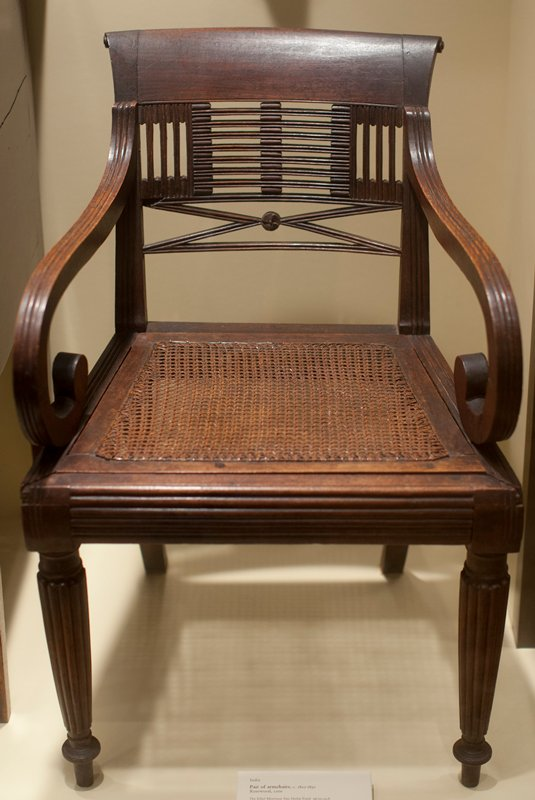 circular fluted front legs; scrolled upper back splat; arms fluted and curl under in front; caned seat panel which removes