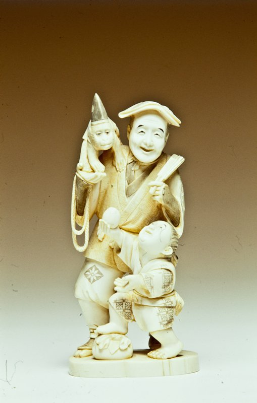 carved figural group of a man with monkey on his shoulder and a boy holding an egg