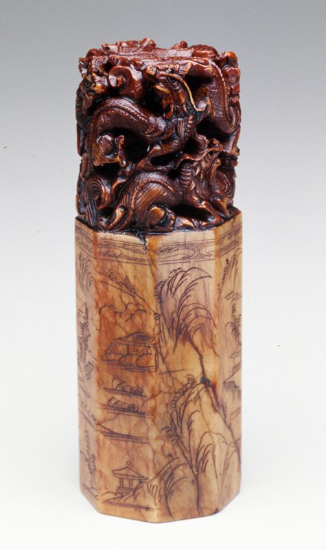 brown stone, upper 3/8 intertwined dragons carved in the round; lower 5/8 octagonal with incised outdoor scene; uncarved botton; has own box; purchased with BBD funds by Qi Xiyu