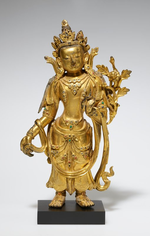 standing gilt bronze figure in contraposto position, proper left hand in front of body with fingers together pointing upward, right hand down at side holding draped fabric
