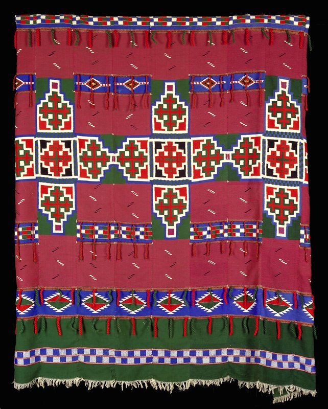 cotton plain weave with weft design of red, white, blue and green geometric shapes with red and green fringe hanging off the surface and white fringe at ends