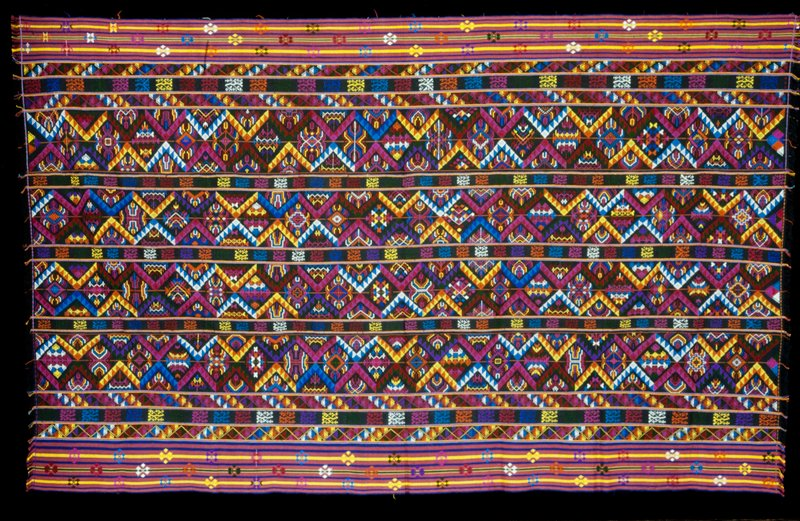 Kira, Oshem; silk/cotton brocade on blue or black cotton background; L.95 in., W.58 in. 3 panels, multicolored discontinuous weft pattern in wool on black cotton background with red, blue, yellow, green stripes at sides; fringe.