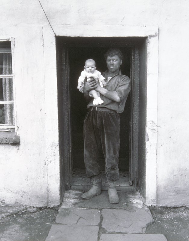man with blackened face in doorway holding baby with light colored clothes.