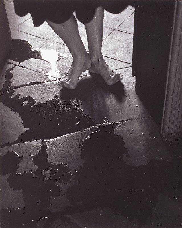 woman's bare feet in doorway, water on floor; one of fifteen prints in portfolio