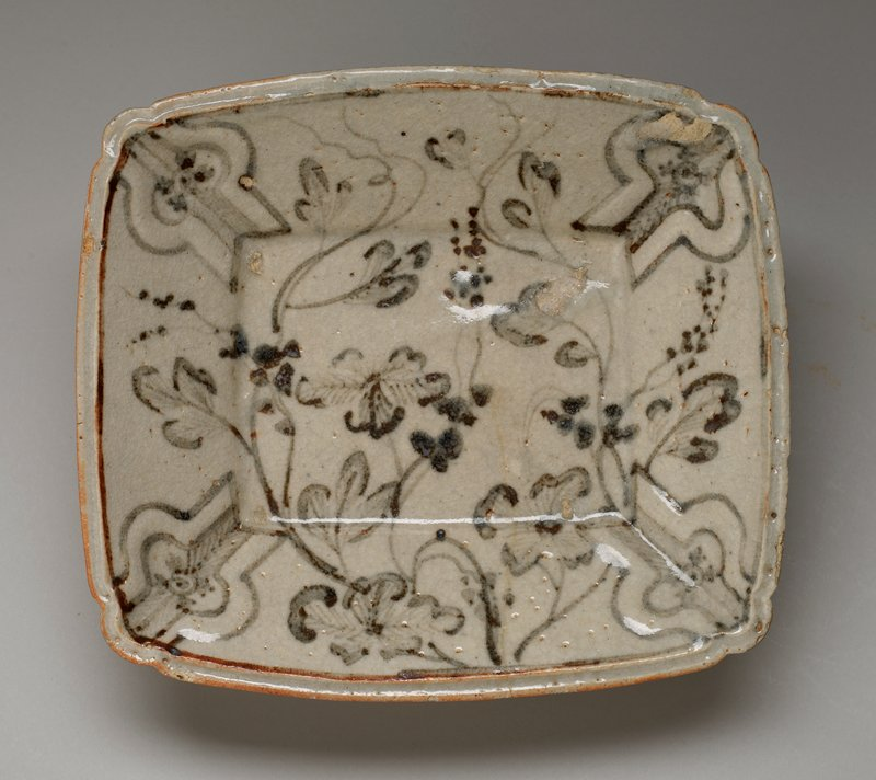 shallow stoneware bowl of rounded rectangular form, four feet; decorated with an underglaze iron oxide pattern of hanging vines and fruit which appear grey and russet under the finely crackled, milky white shino glaze; has storage box