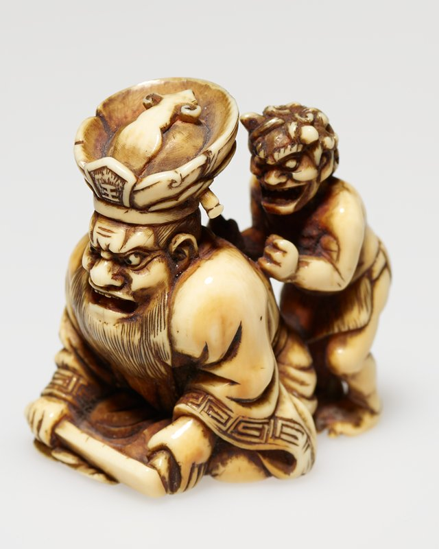 angry faced man with long beard, waering elaborate hat and holding a paddle, being given a back massage by a small standing demon