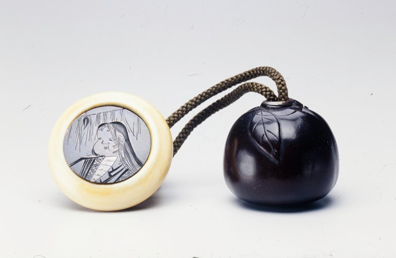 metal disk with shallow carving of a portrait of a chubby-faced woman; disk fits into ivory holder; netsuke in the shape of a peach which opens to reveal two men playing go; all parts attached together with green cord