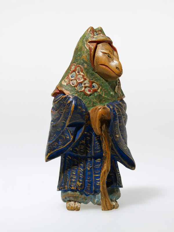 standing figure with fox head wearing green patterned headscarf and blue and gold kimono and resting her proper left hand on a staff