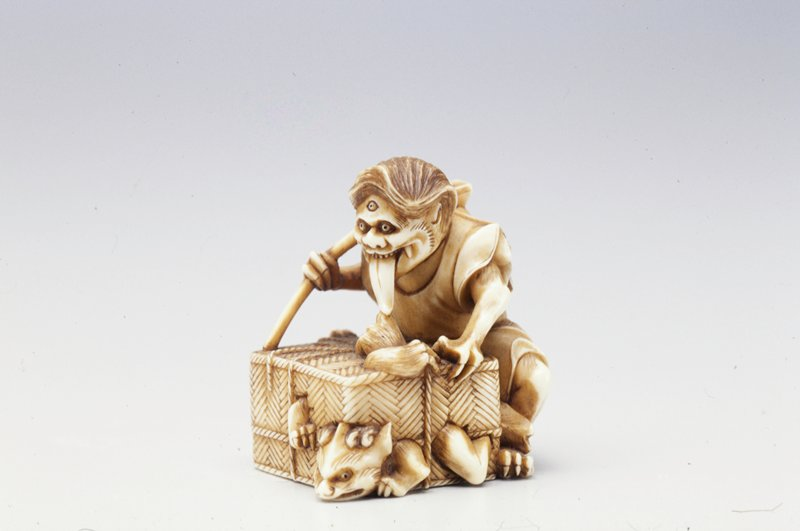 three-eyed, long-tongued figure with a staff slung across its proper right shoulder squats behind a wicker basket with an animal-like demon bursting out of the proper right side