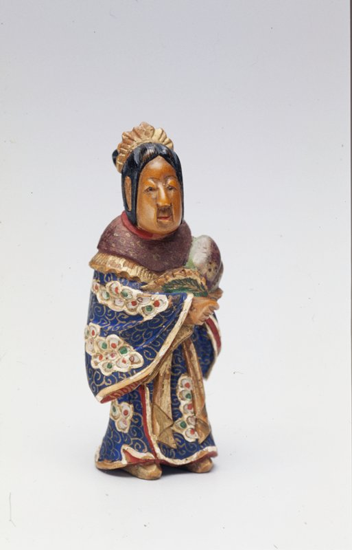 woman with gold hair ornament and dressed in elaborately patterned robe of blue, red, gold, green and white holds a large peach wrapped in leaves in the crook of her proper left elbow