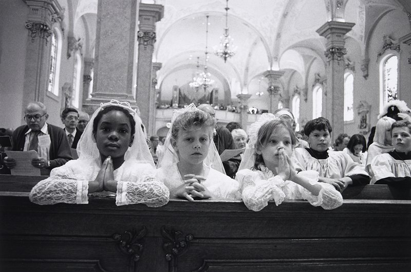 black and white photo of three girls in white dresses and veils in foreground praying