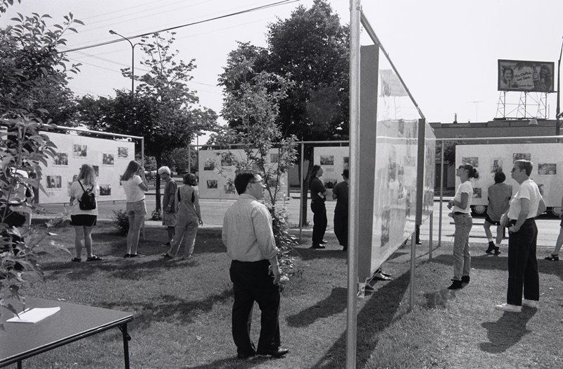 black and white photo of people looking at art exhibition outside