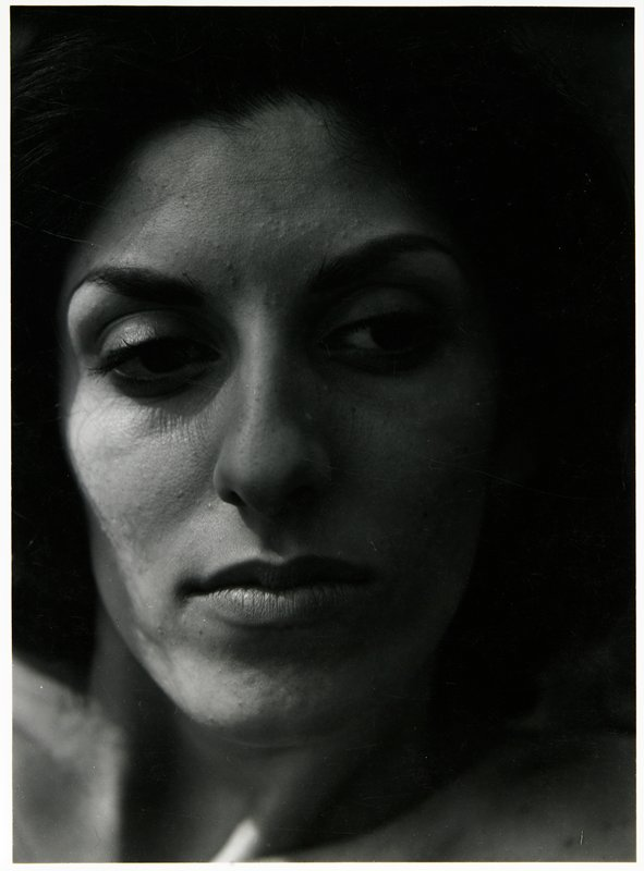 close up of woman's face, looking down to her left