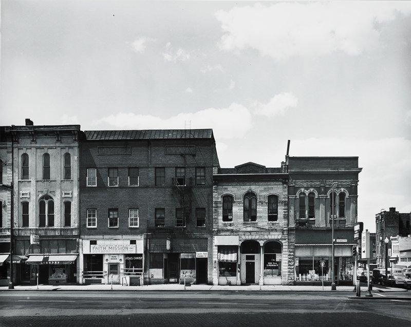 block of store fronts seen from across an empty street (Hennepin Avenue)