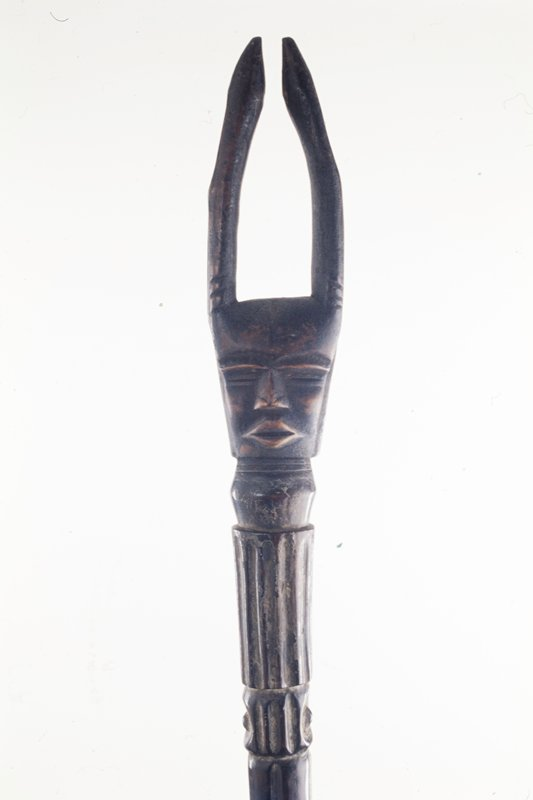 Staff with face with long horns at top of a shaft with incised vertical ribs, diagonal lines and rings